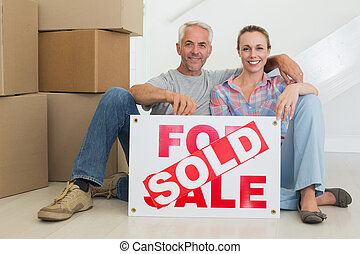 Happy couple sitting on floor with sold sign in their new...