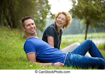 Happy couple sitting on grass outdoors