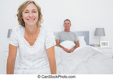 Happy couple sitting on opposite ends of bed