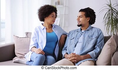 happy couple sitting on sofa and talking at home