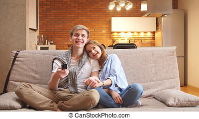 Happy couple sitting on the couch watching tv together at home in living room.