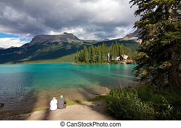 Happy couple sitting on the shore of Emerald Lake in Yoho National Park