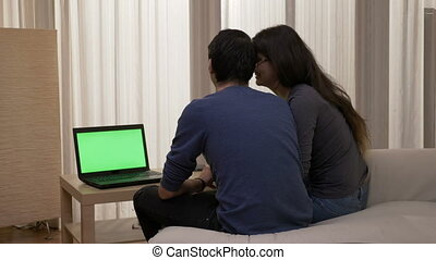 Happy couple sitting on the sofa with a laptop watching a movie kissing and laughing at home in bedroom