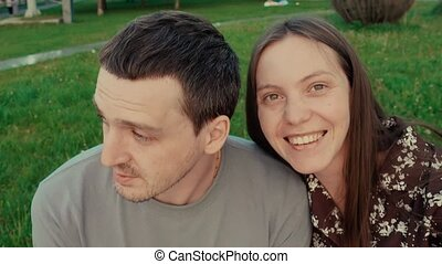Happy couple sitting relaxed on grass - Crop view of...