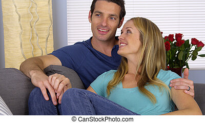 Happy couple sitting together on couch