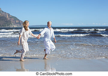Happy couple skipping barefoot on the beach on a sunny day