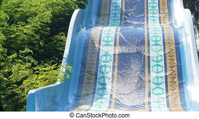 Happy couple sliding down water slide smiling in sunny...