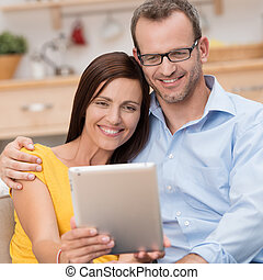 Happy couple smiling and reading their tablet-pc