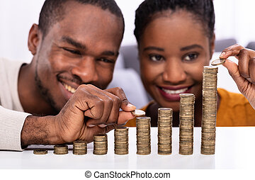Happy African Couple Stacking Coins Over White Desk
