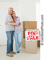 Happy couple standing and hugging beside sold sign