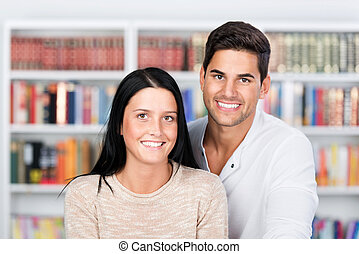 Happy couple standing in front of the bookshelf