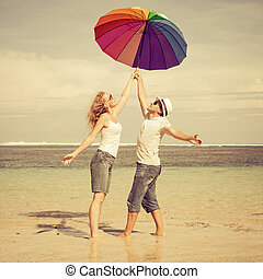 happy couple standing on the beach at the day time