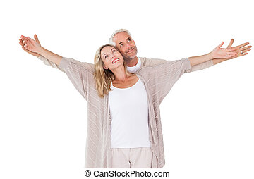 Happy couple standing with arms outstretched on white...
