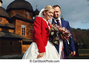 Happy couple stands in the front of a wooden church