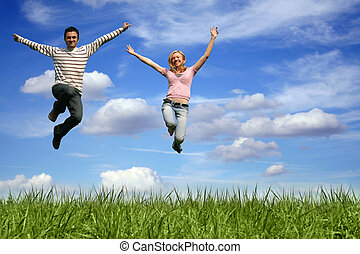 happy couple - a happy young couple - team is jumping in the...