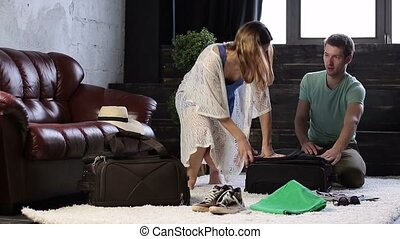 Happy couple struggling to close stuffed suitcase