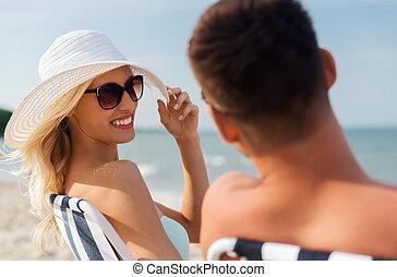 happy couple sunbathing on summer beach