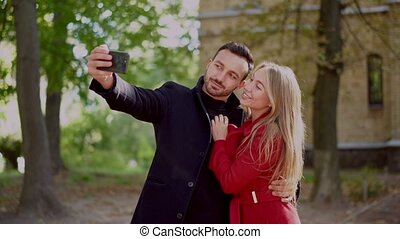 Happy couple takes selfie on the smartphone. - Cheerful...