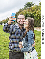 Happy Couple taking a selfie in a French Garden - Young ...