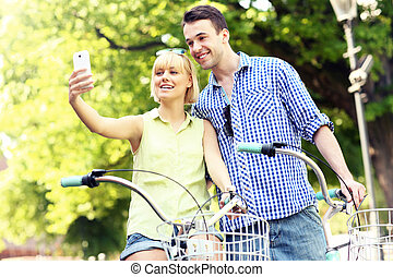 A picture of a happy couple taking pictures of themselves on a bike