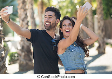 Happy couple taking selfie by mobiles