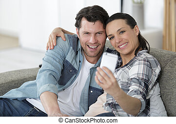happy couple taking selfie on sofa at new home
