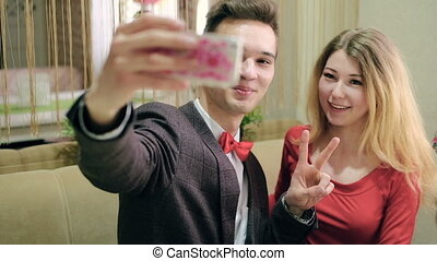 Happy couple taking selfie photo with cellphone