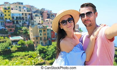 Happy couple taking selfie with view of the old coastal town background of Corniglia, Cinque Terre national park, Liguria, Italy ,Europe