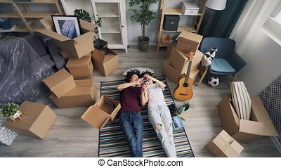 Happy married couple is taking things from box lying on carpet relaxing on florr during relocation. Moving to new house, youth lifestyle and millennials concept.