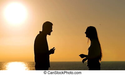 Happy couple talking at sunset on the beach