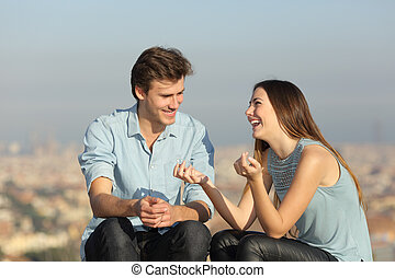 Happy couple talking in a sunny day in a city outskirts