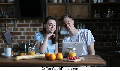 Happy couple talking over video call using laptop