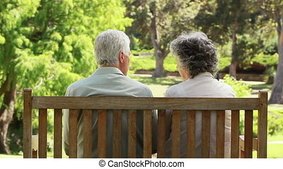 Happy couple talking together while sitting on a bench