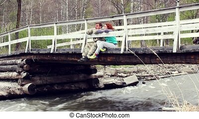happy couple talking while sitting on a wooden bridge