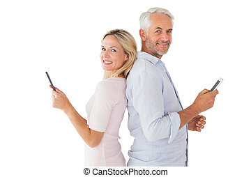 Happy couple texting on their smartphones on white...