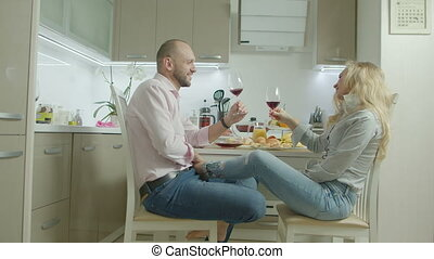 Happy couple toasting with red wine in kitchen - Carefree...