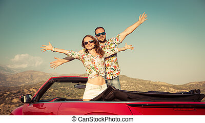 Happy couple travel by car in the mountains