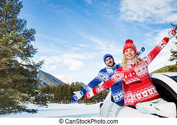 Happy couple travel by car in winter - Happy couple travel...