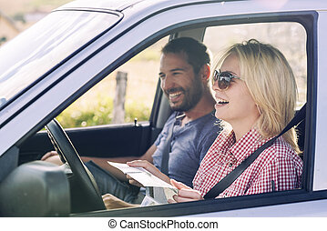 Happy couple traveling by car in nature and looking in map. Carefree friend travelers on countryside roadtrip journey.