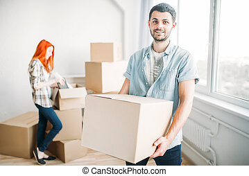 Happy couple unpacking cardboard boxes, new house
