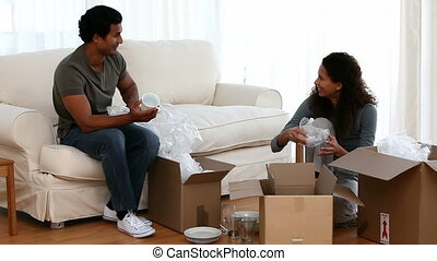 Happy couple unpacking in the living room
