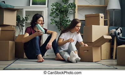 Happy couple is unpacking things after relocation opening box and looking at photos talking sitting on floor together. Moving to new house and relationship concept.