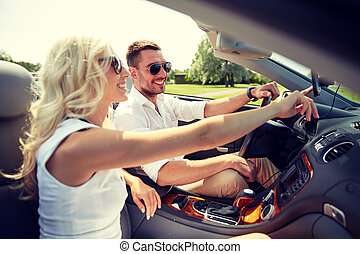 happy couple using gps navigator in cabriolet car