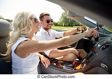 happy couple using gps navigator in cabriolet car