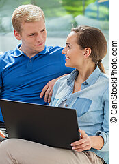 Happy couple using internet at home