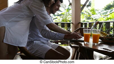 Happy Couple Using Laptop On Summer Terrace Typing Message Together, Woman Embracing Man Sitting At Table Happy Smiling