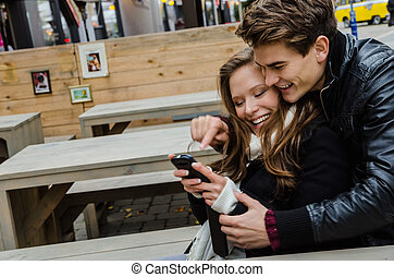 Happy Couple Using Mobile Phone Together