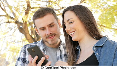 Happy couple using smart phone in a park