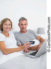 Happy couple using their laptop to buy online
