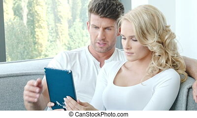Happy Couple Using Touch Pad While Sitting on Couch at Their...